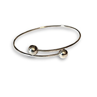 a sterling silver bangle with two balls