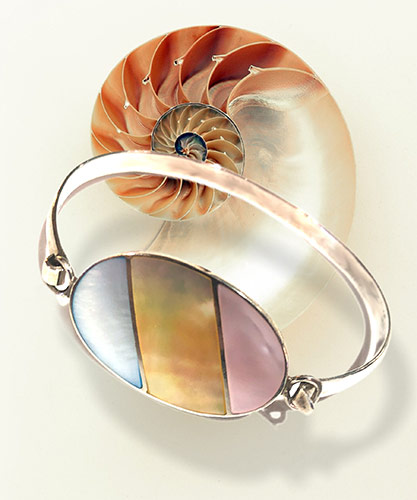 three mother of pearls on a silver bangle