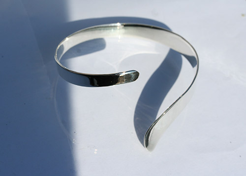 silver bangle with a curved twist