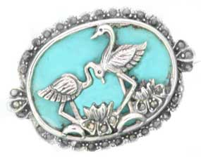 pair of flamingos on a turquoise backround set on a silver brooch
