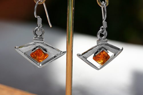 silver earring in the shape of an eye with an amber
