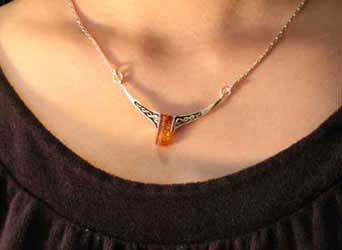 silver celtic amber necklace on ladies neck